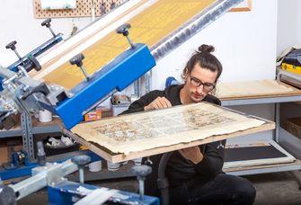 Dennis Blumenstein bei der aufwändigen Herstellung der Replik des Papyrus Ebers per Siebdruckverfahren in der Leipziger Werkstatt von Schmidt, Blumenstein GbR.