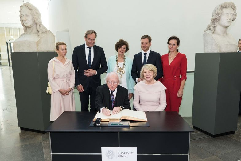 Irish President Michael D. Higgins and his wife Sabina sign the Leipzig University visitors' book. Back row (from left): Ayleena and Burkhard Jung, Beate Schücking and Michael Kretschmer with partner Annett Hofmann.