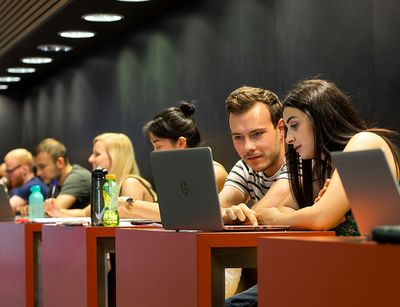 Students with computers inside the lecture hall building