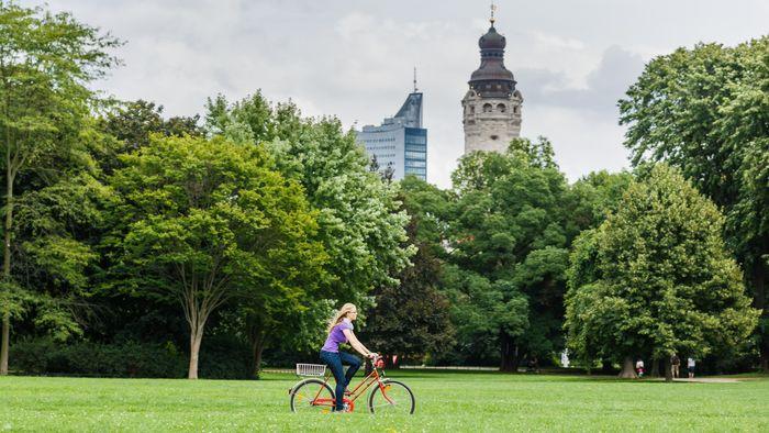 Junge Frau fährt mit dem Fahrrad durch den Park. Im Hintergrund ist das Neue Rathaus in Leipzig zusehen.