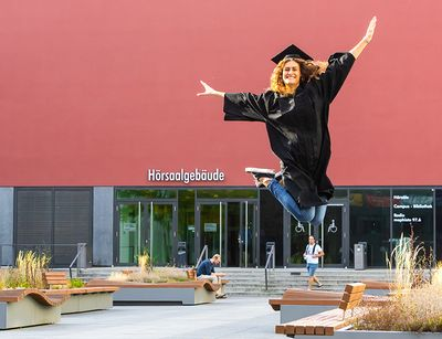 Graduate jumping for joy