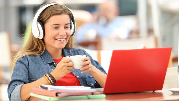 Junge Frau mit Laptop und Kopfhörern, Foto: Colourbox