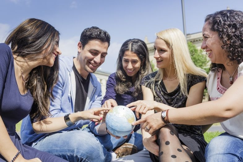 International students point at globe