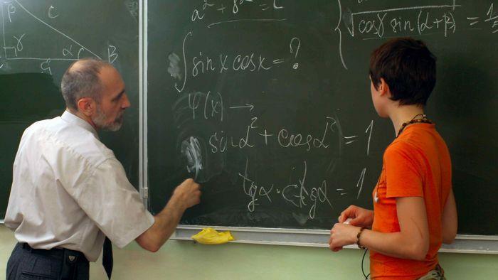 Schülerin bekommt vom Lehrer eine Mathe-Aufgabe erklärt.