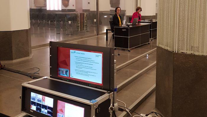 Dr. Claudia Maicher und Rektorin Beate Schücking an einem Redepult im Paulinum, im Vordergrund ein Laptop zur Übertragung des Livestreams.