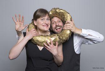 Foto von zwei Kabarettisten die ihre Köpfe durch einen Siegeskranz stecken.