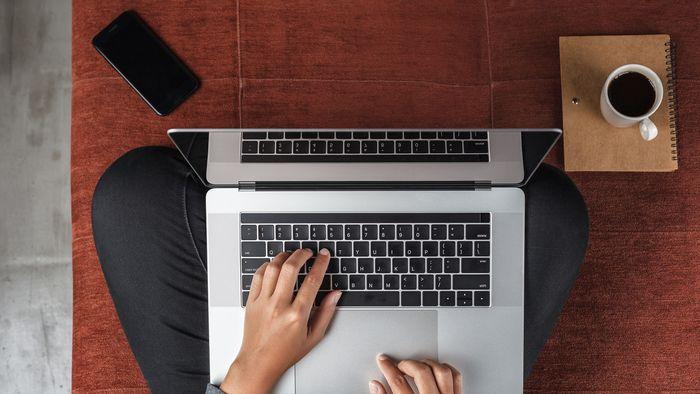 Vorgelperspektive auf einen Menschen, der im Schneidersitz auf dem Fußboden sitzt. Auf dem Schoß steht der Laptop. Die Hände liegen auf der Tastatur und tippen. Der Rest vom Körper ist nicht zu sehen.