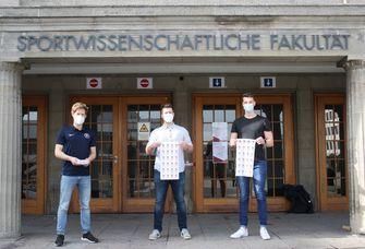 Auf dem Foto sind zwei Sportstudenten zu sehen, die von ihrem Dozenten Michael Fuchs (links) stellvertretend für ihre Teams für ihre innovativen Konzeptideen zum Olympic Day mit einem Team-Deutschland-Schlauchtuch ausgezeichnet wurden.