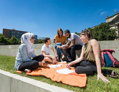 Students are seen relaxing outside on a blanket.
