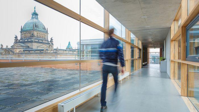 Foto: ein Mann ist auf den Gängen eines Gebäudes unterwegs. Durch die Glasfasade sieht man im Hintergrund das Bundesverwaltungsgericht.