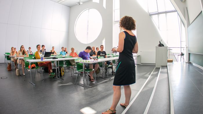 Frau, von hinten zu sehen, steht im Seminarraum und hält einen Vortrag