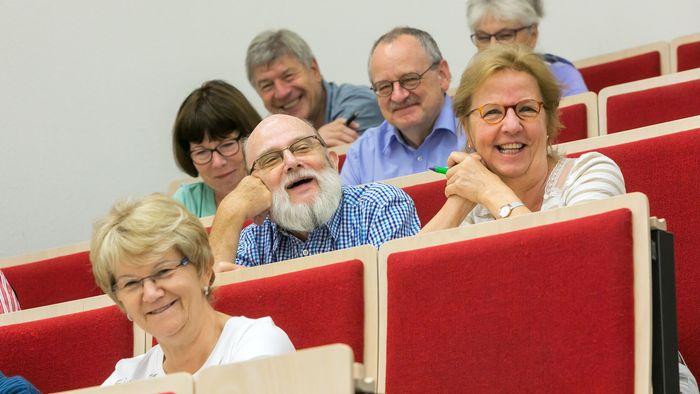 Lächelnde Teilnehmerinnen und Teilnehmer des Seniorenkollegs im Audimax