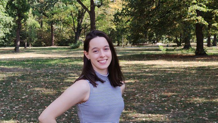 Sophie Effertz steht im Park und lächelt in die Kamera.