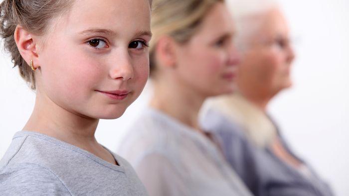 Drei Personen aus verschiedenen Generationen vom Kind bis zur Seniorin sitzen hintereinander..
