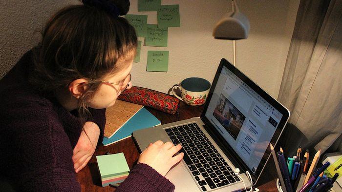 Das Bild zeigt eine Studierende zu Hause am Laptop.