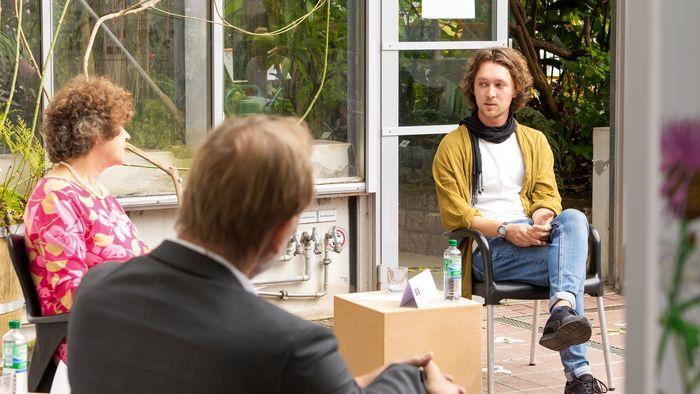 Das Bild zeigt Pavel Raus (rechts). Er sitzt neben Rektorin Beate Schücking und Leipzigs Oberbürgermeister Burkhard Jung und gehört zu den geförderten Studierenden im Rahmen der Aktion SiS.