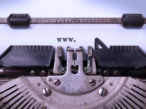 Close-up of a typewriter which has been use to type WWW on a white sheet of paper.