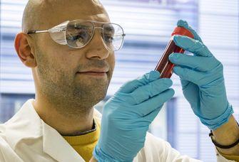 Majd Al-Naji mit Schutzbrille hält Röhrchen mit roter Flüssigkeit hoch, Foto: Dr. Nieves Lopez Salas