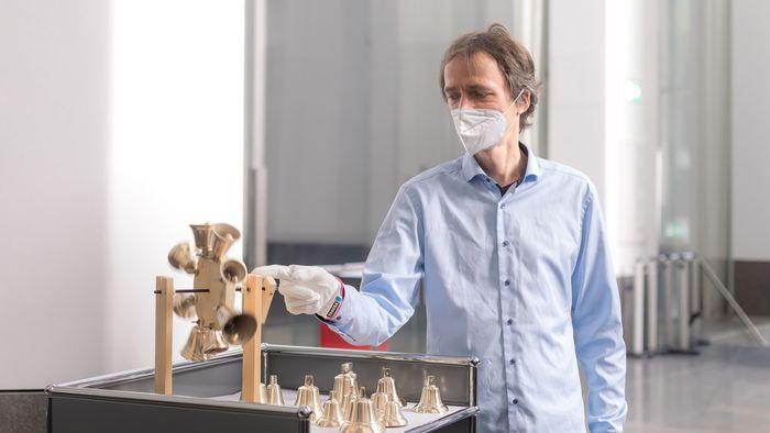 Universitätsmistikdirektor David Timm schaut sich eines der neuen Glockenräder für die Schwalbennestorgel an.