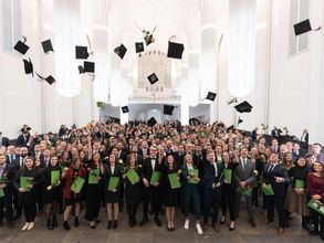 Graduates are seen throwing mortarboards in the air during the Faculty of Law's 2020 graduation ceremony in the Paulinum.